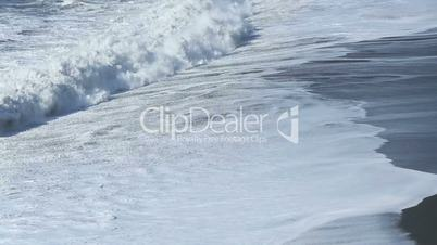 Waves at the black sand beach coast in Vik, Iceland