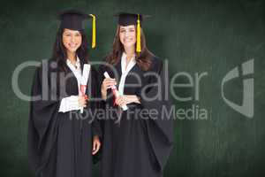 Composite image of full length shot of two women graduating