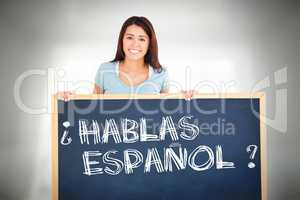 Composite image of attractive woman holding a  board