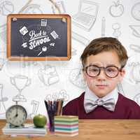 Composite image of cute schoolboy wearing reading glasses