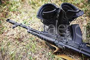 soldier ankle boots and a Kalashnikov assault rifle close-up