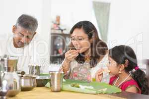 Indian family eating banana leaf rice