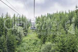 Lift in the mountain. Fir forest. Summer time