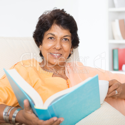 Happy Indian mature woman reading book