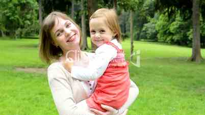 pretty mother with cute daughter smile to camera - park