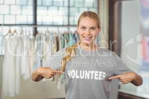 Portrait of happy woman showing volunteer text on tshirt