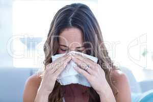 Sick woman sneezing in tissue