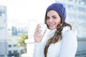 Cold brunette in warm clothes drinking coffee
