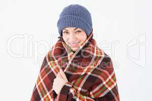 Smiling brunette with checked blanket