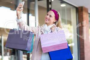 Smiling woman with shopping bags taking selfies