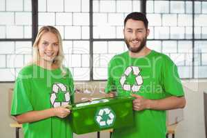 Portrait of smiling volunteers carrying recycling container
