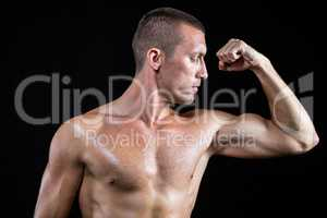 Serious shirtless athlete flexing muscles