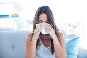 Sick woman sneezing on sofa