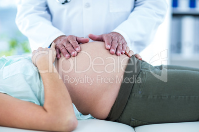Doctor examining pregnant woman in clinic