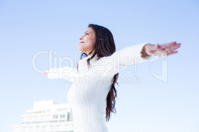 Pretty brunette feeling the air with arms raised up