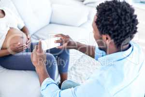 Husband photographing pregnant woman at home