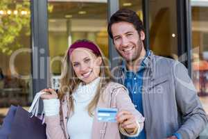 Smiling couple with shopping bags showing credit card