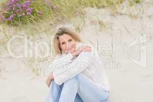 Woman sitting near the sandy hill