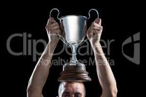 Successful rugby player holding trophy