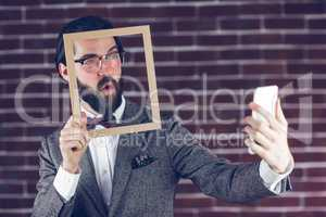 Fashionable man taking selfie while holding frame