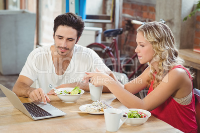 Man and woman discussing during coffee break in office