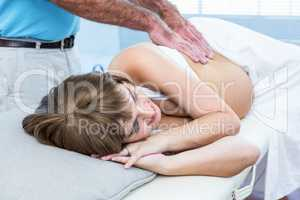 Masseur massaging pregnant woman