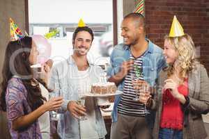 Portrait of smiling businessman holding cake during birthday cel