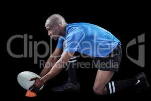 Rugby player keeping ball on kicking tee
