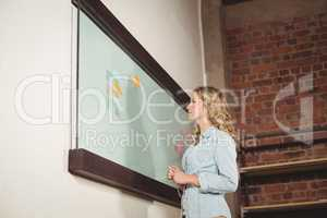 Low angle view of businesswoman standing by glass board in offic