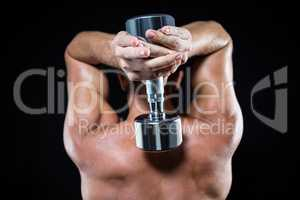Rear view of shirtless sports player working out with dumbbell