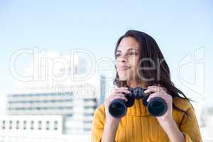 Pretty brunette holding binoculars