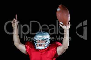 American football player with arms raised holding ball
