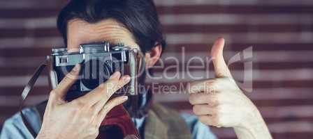 Man showing thumbs up gesture while photographing