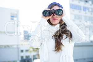 Cold brunette in warm clothes using binoculars