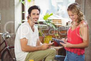 Portrait of businessman with smart phone while woman using digit