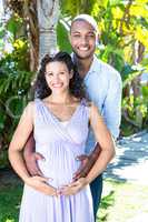 Portrait of happy husband with pregnant wife touching belly