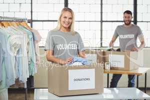 Volunteer separating clothes from donation box