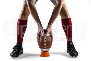 Low section of sports player placing the ball