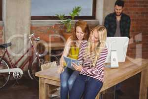 Women using digital tablet while man working on computer