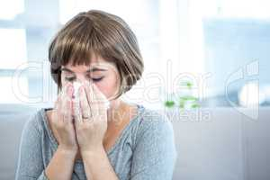 Woman sitting on a sofa about to sneeze