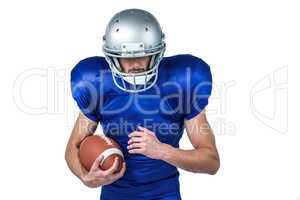 Sports player wearing helmet while holding ball