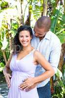 Portrait of happy pregnant wife with husband touching belly
