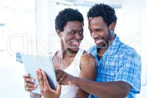 Husband pointing towards digital tablet at home