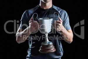 Victorious rugby player holding trophy