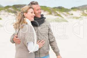 Happy couple embracing by the shore