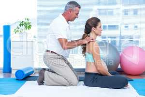 Gym trainer massaging pregnant woman