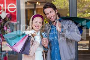 Smiling couple with shopping bags in front of window
