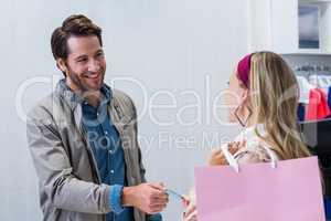 Smiling cashier handing back credit card