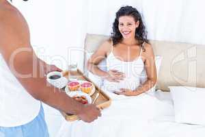 Husband with breakfast tray for pregnant wife