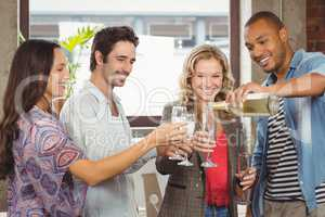 Smiling businessman pouring champagne in glass